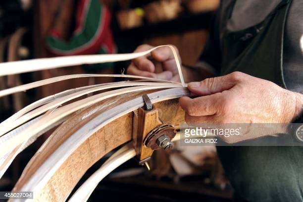 JeanLouis Gonzalez works on a chistera used to play the Basque pelota game on September 3 2014 in his workshop in Anglet southern France The 17th...