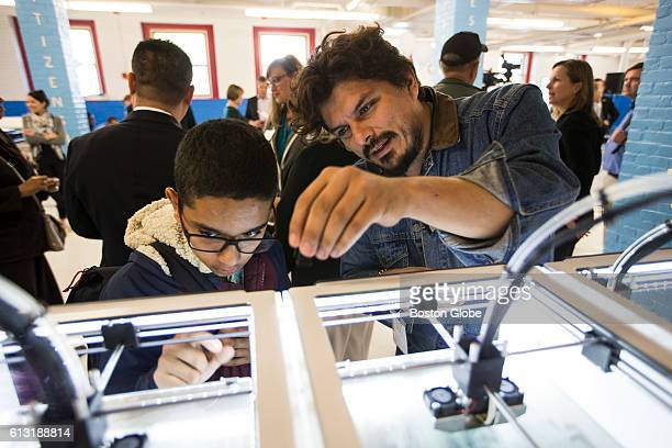 JeanLuc Pierite from the Fab Foundation shows a 3D printer to a student during an event to announce the debut of General Electric's mobile Brilliant...