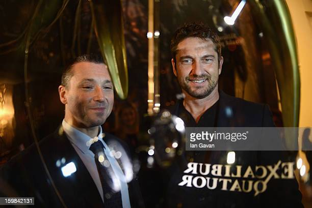 JeanMarc Pontroue CEO of Roger Dubuis looks at the Excalibur Quatuor watch with actor and friend of the brand Gerard Butler as he visits the Roger...