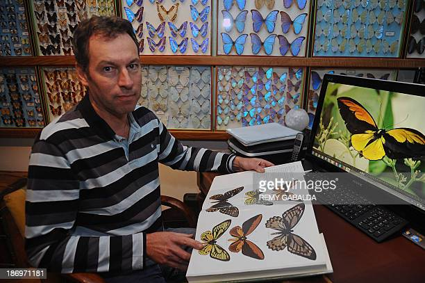 JeanMarc Sor a French entomologist who crossed the globe to take pictures of a giant rare butterfly on an Indonesian island poses with a book showing...