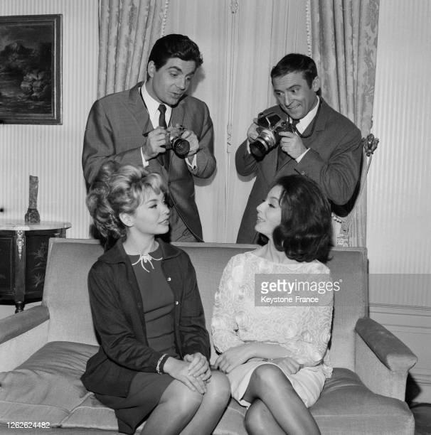 Jean-Marc Thibault et Roger Pierre debout, appareils photo en main, photographient Patricia Viterbo et Claudine Coster assises sur un canapé, en...