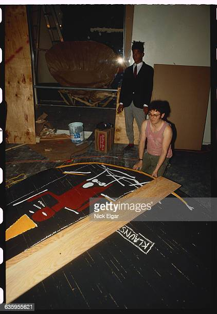 JeanMichel Basquiat looks on as a woman inspects his artwork at Area a Manhattan nightclub