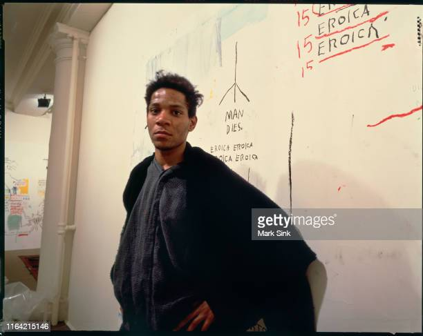 JeanMichel Basquiat stands in front of his painting with the words Man Dies on exhibit at the Vreg Baghomian Gallery shortly before his death August...