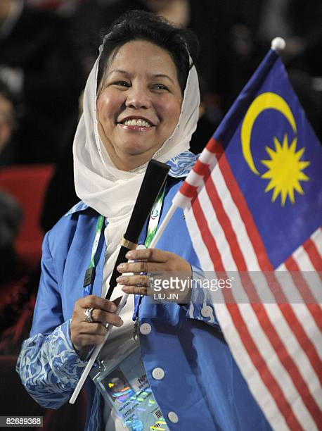 Jeanne Abdullah wife of Malaysian Prime Minister Abdullah Ahmad Badawi smiles while holding the Malaysian national flag during the opening ceremony...