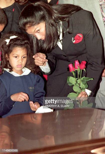 Jeanne Ashe wife of the late Arthur Ashe points out to daughter Camera as the casket of Ashe is lowered into the ground 10 February 1993 during...