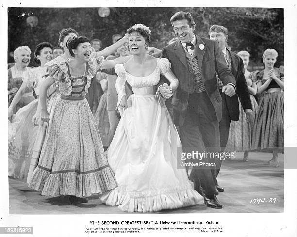 Jeanne Crain and George Nader at a formal event having fun in a scene from the film 'The Second Greatest Sex' 1955