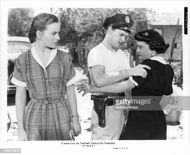 Jeanne Crain looking towards Nina Mae McKinney, who's being held by off duty officer in a scene from the film 'Pinky', 1949.