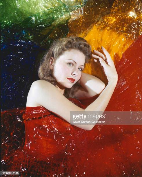 Jeanne Crain US actress posing with sheets of red blue yellow and green cellophane in a studio portrait circa 1955