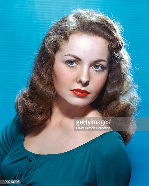 Jeanne Crain US actress wearing a blue top in a studio portrait against a light blue background circa 1950