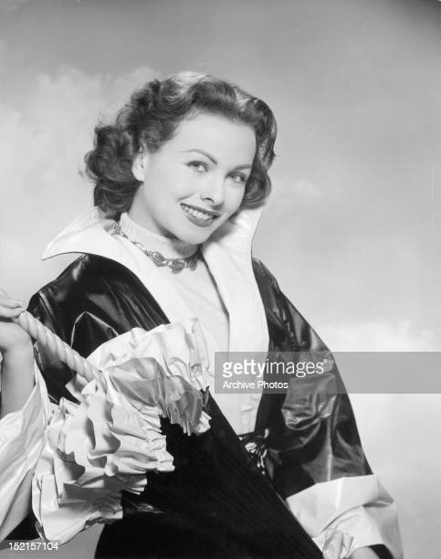 Jeanne Crain with a new type of plastic raincoat and matching umbrella in publicity portrait for the film 'Full House' 1952