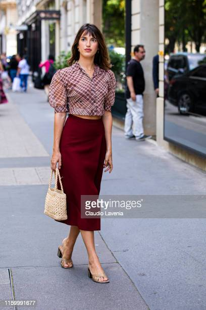 Jeanne Damas, wearing a Dior checked shirt, red midi skirt, straw bag and nude heels, is seen outside Christian Dior show during Paris Fashion Week -...