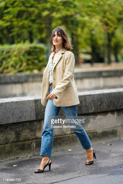 "Jeanne Damas wears a blazer jacket, a shirt with several printed ""v"" letters, blue jeans, heels shoes, outside Valentino, during Paris Fashion Week -..."