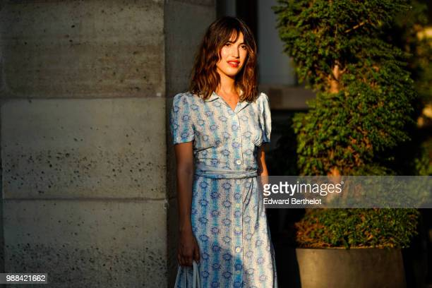 Jeanne Damas wears a blue dress with floral prints a blue bag outside the Miu Miu Cruise Collection show outside the Hotel Regina in Paris on June 30...