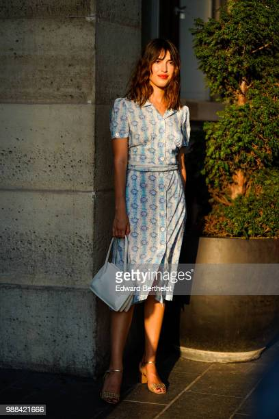 Jeanne Damas wears a blue dress with floral prints, a blue bag, outside the Miu Miu Cruise Collection show, outside the Hotel Regina, in Paris, on...