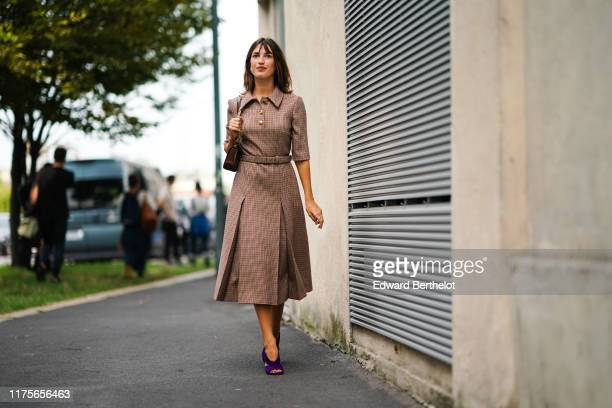 Jeanne Damas wears a brown dress with houndstooth print pattern and golden buttons purple shoes outside the Prada show during Milan Fashion Week...