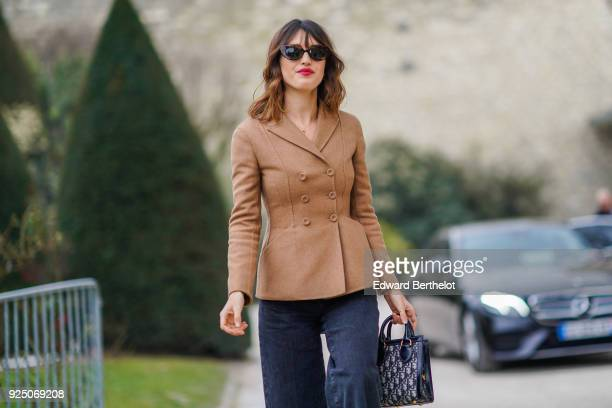 Jeanne Damas wears a brown jacket sunglasses flare pants a bag outside Dior during Paris Fashion Week Womenswear Fall/Winter 2018/2019 on February 27...