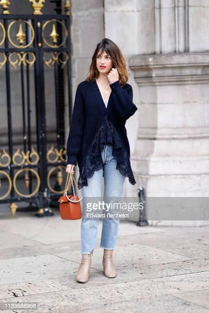 Jeanne Damas wears a dark blue lace wool jacket blue jeans an orange bag outside Stella McCartney during Paris Fashion Week Womenswear Fall/Winter...