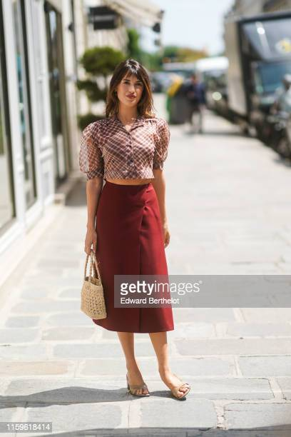 Jeanne Damas wears a Dior puff sleeves brown and red checkered crop shirt, a burgundy wrap-over skirt, a woven sisal bag, taupe-color mules , outside...