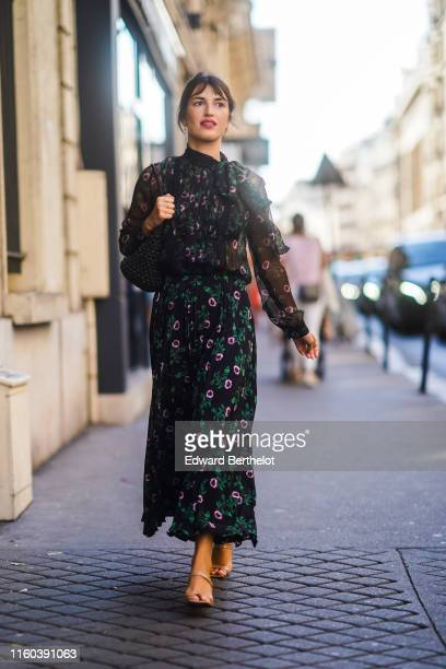 Jeanne Damas wears a floral print black mesh dress, a bag, outside Valentino, during Paris Fashion Week -Haute Couture Fall/Winter 2019/2020, on July...