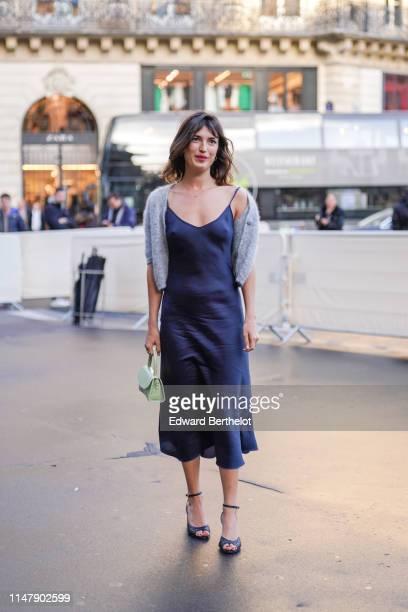 Jeanne Damas wears a gray wool jacket a dark blue silky dress a green bag shoes outside the Opera Garnier 350th Anniversary Gala in Paris on May 08...