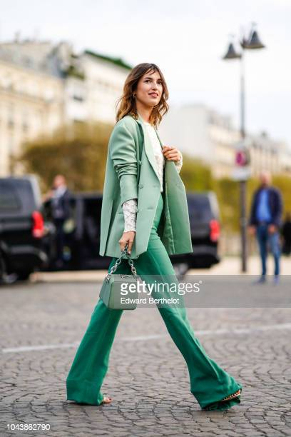 Jeanne Damas wears a green blazer jacket a bag flare pants outside Valentino during Paris Fashion Week Womenswear Spring/Summer 2019 on September 30...