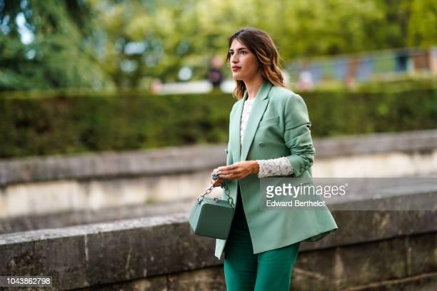 Jeanne Damas wears a green blazer jacket a bag flare pants outside Valentino during Paris Fashion Week Womenswear Spring/Summer 2019 on September 30...
