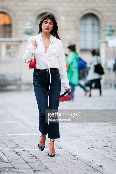 Jeanne Damas wears a white shirt a red bag and dark pants outside of the Sonia Rykiel show during Paris Fashion Week Spring Summer 2017 on October 3...