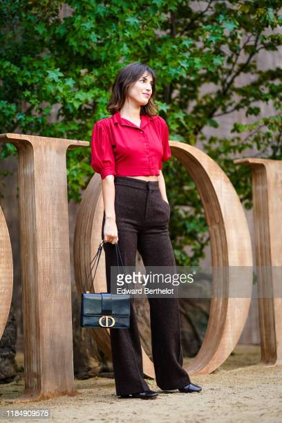 Jeanne Damas wears earrings, a red crop shirt with puff short sleeves, dark brown pants, a black Dior bag, black crocodile pattern shoes, outside...