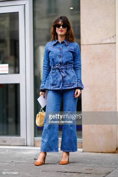 Jeanne Damas wears sunglasses a blue denim jacket blue flare jeans brown shoes a bag during Paris Fashion Week Womenswear Fall/Winter 2018/2019 on...