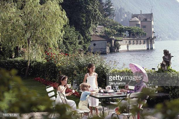 Jeanne Marie Drouleurs, shading herself beneath a parasol, while taking tea with three young children at the Villa Belvedere, on the shores of Lake...