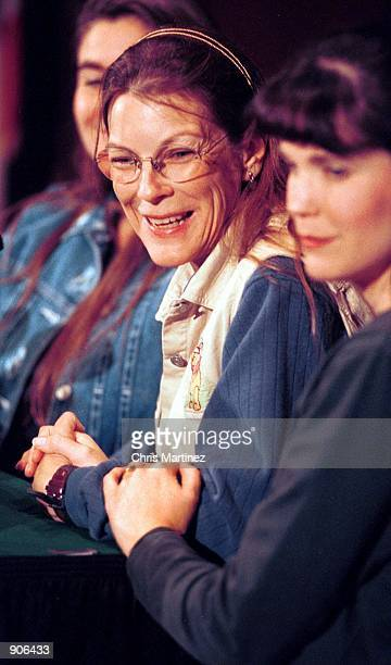 Jeanne Moore the sole American hostage aboard an Indian Airlines flight holds her daughter Michelle Twisselman's hand as she answers reporters...