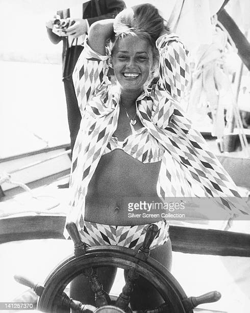Jeanne Moreau French actress wearing a diamond print pattern bikini and matching blouse smiling as she poses by the wheel of a boat with her arms...