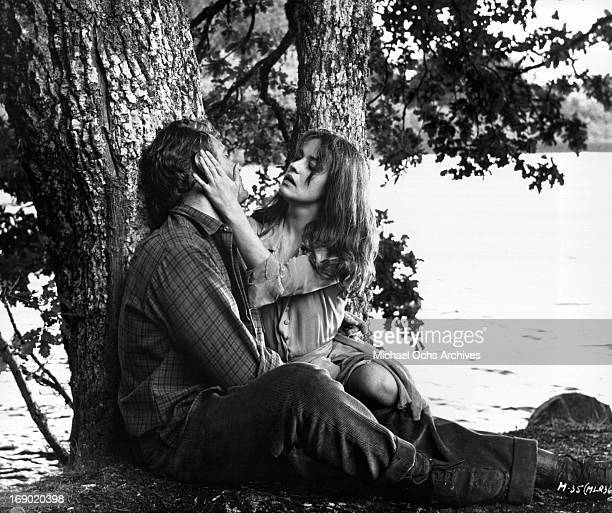 Jeanne Moreau with her hands on Ettore Manni's face as they sit under a tree in a scene from the film 'Mademoiselle' 1966