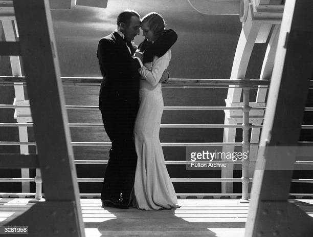 Jeanne Stuart and Tom Walls share a moonlight clinch on the deck of a liner in a scene from the film 'Leap Year' directed by Tom Walls for the...