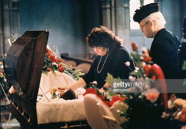 Jeanne White puts her hand on the body of her son Ryan just before visitation starts 4/11. At right is singer Elton John, a friend of the family....