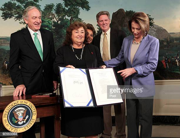 Jeanne WhiteGinder Ryan White's mother holds the Ryan White HIV/AIDS Treatment Extension Act of 2009 after President Barack Obama signed it flanked...