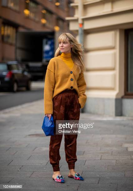 Jeannette Madsen wearing mustard cardigan and turtleneck jogger pants with print blue clutch is seen during Stockholm Runway SS19 on August 28 2018...