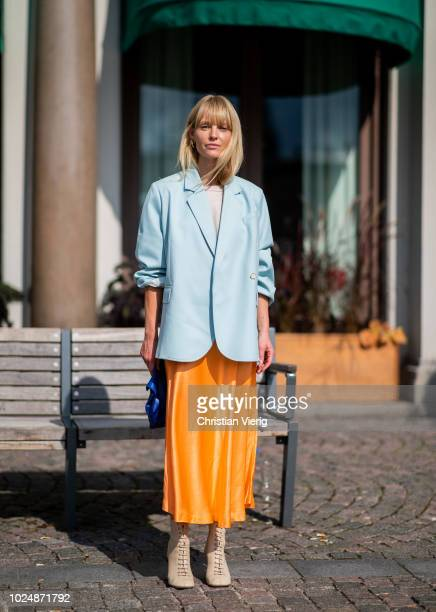 Jeannette Madsen wearing orange midi skirt, ankle boots, light blue blazer, navy clutch is seen during Stockholm Runway SS19 on August 28, 2018 in...