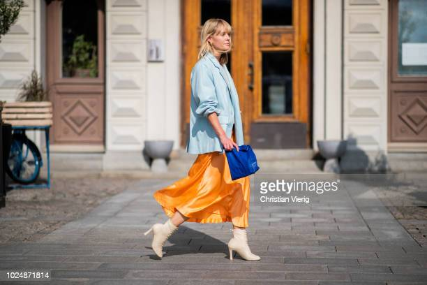 Jeannette Madsen wearing orange midi skirt ankle boots light blue blazer navy clutch is seen during Stockholm Runway SS19 on August 28 2018 in...