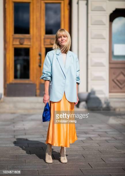 Jeannette Madsen wearing orange midi skirt ankle boots light blue blazer navy clutch is seen during Stockholm Runway SS19 on August 28 2018 in...