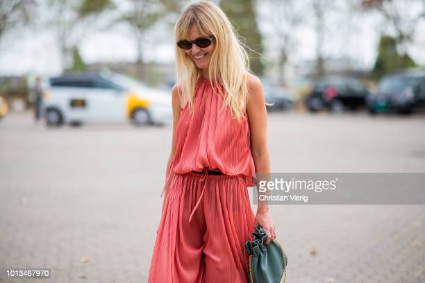 Jeannette Madsen wearing red jumpsuit is seen outside Holzweiler during the Copenhagen Fashion Week Spring/Summer 2019 on August 8, 2018 in...