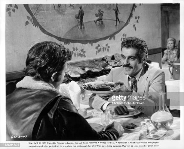 JeanPaul Belmondo and Omar Sharif share a meal in a scene from the film 'The Burglers' 1971