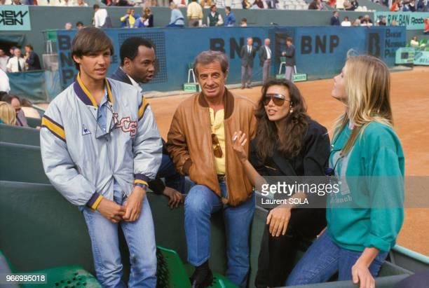 JeanPaul Belmondo au stade RolandGarros lors des Internationaux de France de tennis avec son fils Paul et son amie Carlos SottoMayor le 25 mai 1986 à...