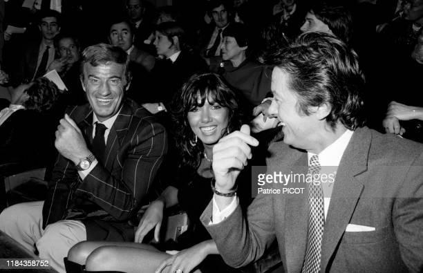 JeanPaul Belmondo avec sa compagne Carlos Sotto Mayor et Alain Delon à la 1ère du spectacle de Thierry le Luron à Paris en 1982 France
