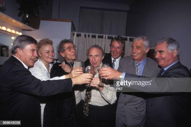 JeanPaul Belmondo Guy Bedos Alain Delon Darry Cowl JeanClaude Brialy et Pierre Richard entourent Muriel Robin dans sa loge en novembre 1994 à Paris...