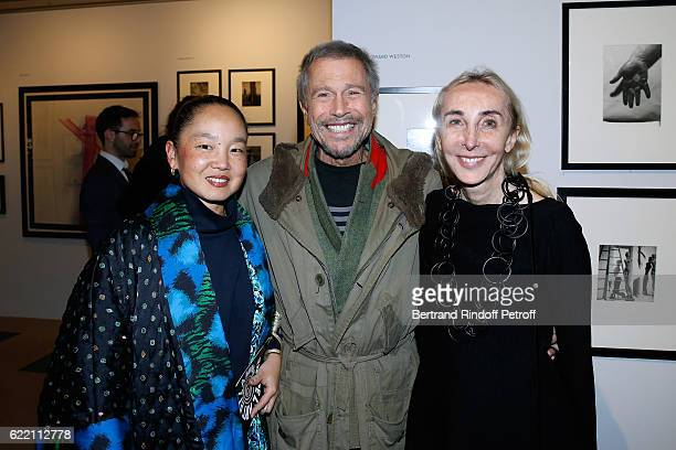 JeanPaul Goude standing between his wife Karen Park Goude and Carla Sozzani attend the Carla Sozzani Photo Exhibition at Azzedine Alaia Gallery on...