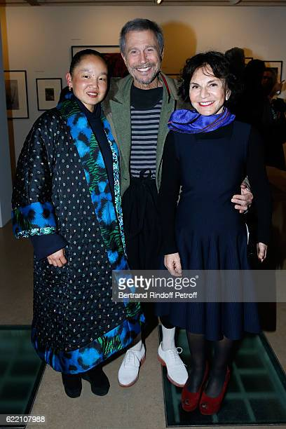 JeanPaul Goude standing between his wife Karen Park Goude and Monique Lang attend the Carla Sozzani Photo Exhibition at Azzedine Alaia Gallery on...