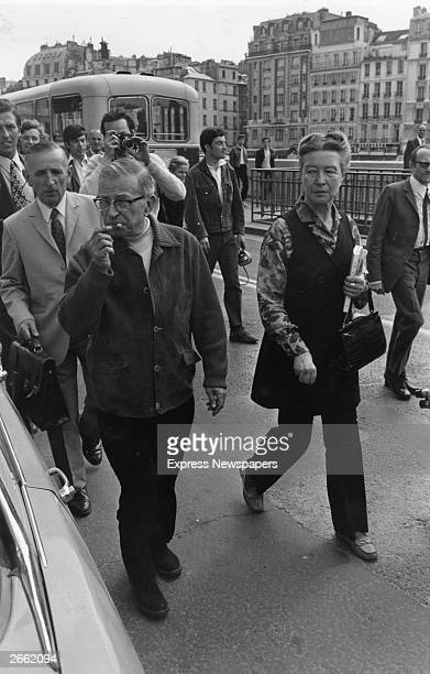 JeanPaul Sartre French existentialist philosopher and writer walking with French novelist Simone de Beauvoir to the Palais de Justice in Paris...