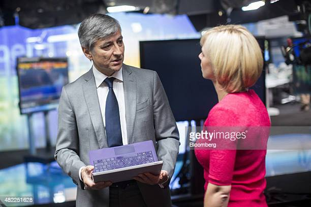 JeanPhilippe Courtois president of Microsoft International holds a Microsoft Corp Surface tablet device as he speaks to Caroline Hyde Bloomberg...