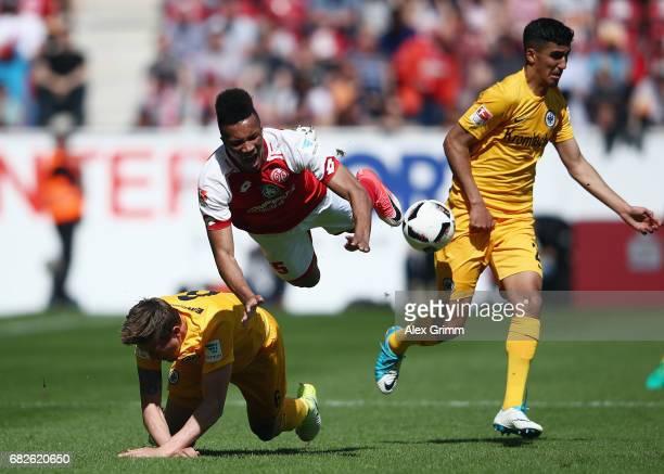 JeanPhilippe Gbamin of Mainz is challenged by Bastian Oczipka and Aymane Barkok of Frankfurt during the Bundesliga match between 1 FSV Mainz 05 and...